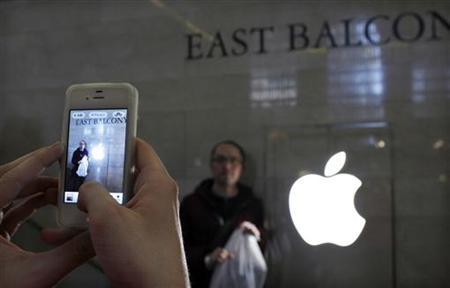 A customer poses next to an Apple logo as he visits the newest Apple Store during its opening on the East Balcony in the main lobby of New York City's Grand Central Station December 9, 2011. REUTERS/Eduardo Munoz