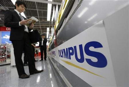 A man is seen next to an Olympus logo at an electronics shop in Tokyo May 10, 2012. REUTERS/Kim Kyung-Hoon