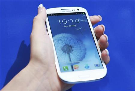 A woman holds up her new Samsung Galaxy S III after it was launched at Westfield in west London, May 29, 2012. REUTERS/Olivia Harris