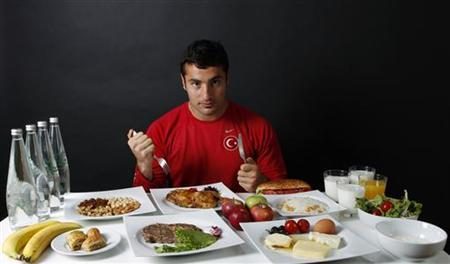 Turkish javelin thrower and Olympic hopeful Fatih Avan, 23, poses in front of his daily meal intake in Ankara May 29, 2012. REUTERS/Umit Bektas