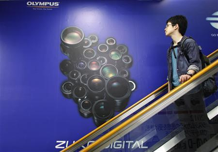 An Olympus Corp advertisement board is seen behind an escalator at an electronics shop in Tokyo June 8, 2012. REUTERS/Toru Hanai