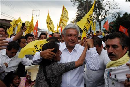 Andres Manuel Lopez Obrador, presidential candidate for the Party of the Democratic Revolution (PRD), is embraced by a supporter as he arrives for a rally in Orizaba, in the Mexican state of Veracruz June 4, 2012. REUTERS/Tomas Bravo
