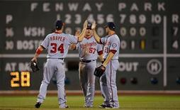 Washington Nationals outfielders Bryce Harper (34), Tyler Moore (C) and Xavier Nady congratulate each other after beating the Boston Red Sox in their MLB Interleague baseball game at Fenway Park in Boston, Massachusetts June 8, 2012. REUTERS/Brian Snyder