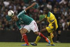 Mexico's Carlos Salcido (L) fights for the ball with Guyana's Christoper Nurse during their 2014 World Cup qualifying soccer match at Azteca stadium in Mexico City June 8, 2012. REUTERS/Edgard Garrido