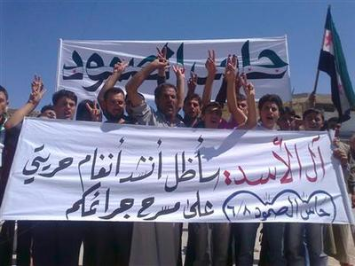 Demonstrators protest against Syria's President Bashar al-Assad after Friday prayers in the northern Syrian city of Hass June 8, 2012. The banner reads, ''Assad's family, we will sing our freedom at your theatre of massacres''. REUTERS/Shaam News Network/Handout