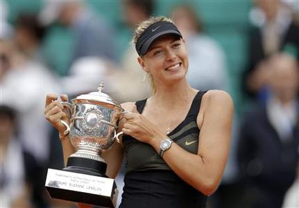 Maria Sharapova of Russia holds the trophy as she poses during the ceremony after defeating Sara Errani of Italy during their women's singles final match at the French Open tennis tournament at the Roland Garros stadium in Paris June 9, 2012. REUTERS/Benoit Tessier