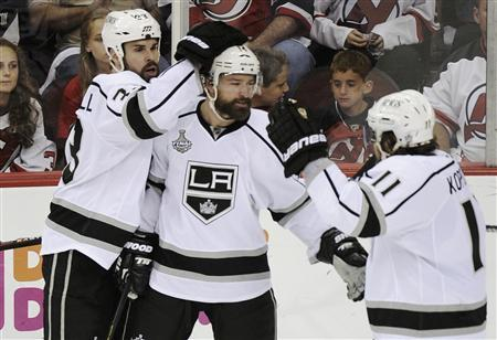 Los Angeles Kings' Justin Williams (C) is congratulated by teammates Willie Mitchell (L) and Anze Kopitar after scoring against the New Jersey Devils during the second period in Game 5 of the NHL Stanley Cup hockey final in Newark, New Jersey, June 9, 2012. REUTERS/Ray Stubblebine