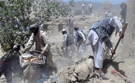 Afghan men search for the bodies of people killed in a NATO airstrike in Logar province June 6, 2012. REUTERS/Stringer