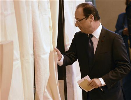 France's President Francois Hollande enters the voting booth in the legislative elections at the polling station in Tulle June 10, 2012. REUTERS/Caroline Blumberg