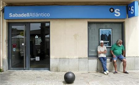 Two men sit outside a bank's window in Alella, June 10, 2012. REUTERS/Albert Gea