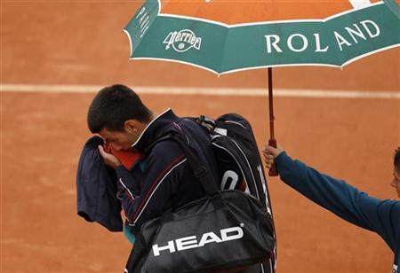 Novak Djokovic of Serbia wipes his face as he leaves the court under an umbrella as rain stops the play during his men's singles final match against Rafael Nadal of Spain at the French Open tennis tournament at the Roland Garros stadium in Paris June 10, 2012. REUTERS/Benoit Tessier