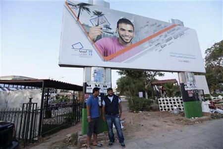 Youths stand in front of an electoral banner showing a man holding a voting card in Benghazi June 4, 2012. REUTERS/Esam Al-Fetori