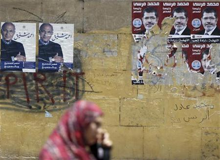 A woman walks past election campaign posters of presidential candidates, Mohamed Mursi, head of the Muslim Brotherhood's political party, and former prime minister Ahmed Shafiq (L), in Cairo June 4, 2012. REUTERS/Amr Abdallah Dalsh