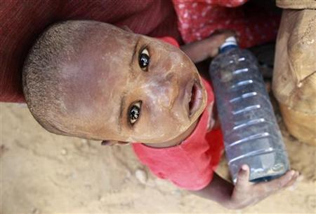 A newly arrived Somali refugee child plays with a water bottle in the Kenya-Somalia border town of Liboi July 29, 2011. REUTERS/Thomas Mukoya