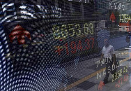A passer-by is reflected in an electronic screen displaying Japan's Nikkei share average, outside a brokerage in Tokyo June 11, 2012. REUTERS/Yuriko Nakao