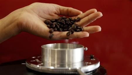 A waitress pours coffee beans into a grinder before she prepares an expresso at a coffee bar in Sao Paulo February 8, 2011. REUTERS/Nacho Doce