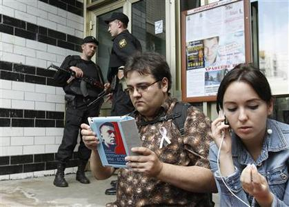 Russian security forces stand guard as an opposition supporter (2nd R) and Anna Veduta, spokeswoman for anti-corruption blogger and opposition activist Alexei Navalny, wait outside the entrance to the apartment block where Navalny lives in Moscow June 11, 2012. REUTERS/Denis Sinyakov