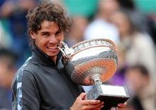 Rafael Nadal, da Espanha, morde troféu durante cerimônia, após derrotar o sérvio Novak Djokovic na final do Aberto Francês no Estádio de Roland Garros, em Paris. 11/06/2012 REUTERS/Nir Elias
