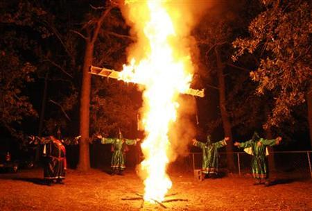 Members of the Ku Klux Klan (KKK) participate in a cross lighting ceremony at a Klansman's home in Warrenville, South Carolina October 23, 2010. REUTERS/Rainier Ehrhardt