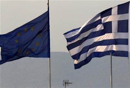 A Greek (R) and an EU flag fly over the Greece's Finance Ministry in Athens November 3, 2011. REUTERS/Yannis Behrakis/Files