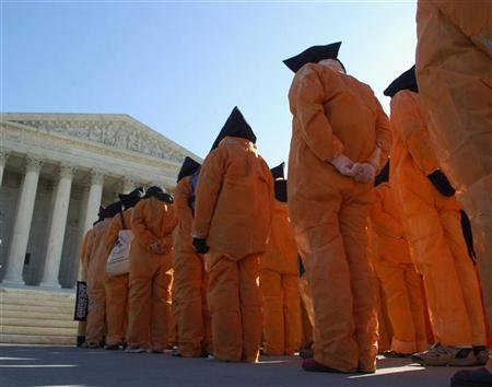 Protesters dressed as prisoners from the U.S. detention facility at Guantanamo Bay march on the U.S. Supreme Court in Washington, January 11, 2007. REUTERS/Jonathan Ernst
