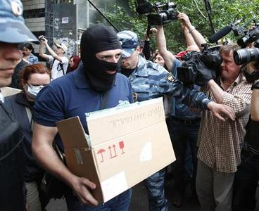 Russian security servicemen leave with items from opposition leader and anti-corruption blogger Alexei Navalny's apartment in Moscow June 11, 2012. REUTERS/Mikhail Voskresensky