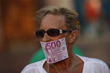 A woman covers her mouth with a fake Euro note during a protest against Spain's bailout at La Constitucion square in Malaga, southern Spain, June 10, 2012. REUTERS/Jon Nazca