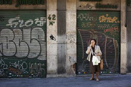 An elderly woman eats a sandwich outside a closed store in Madrid June 11, 2012. REUTERS/Susana Vera