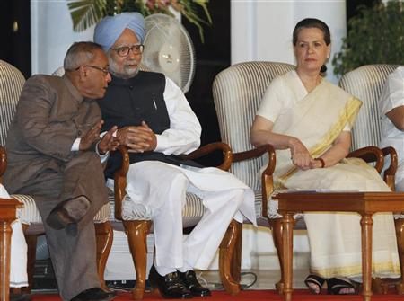 Prime Minister Manmohan Singh (C) speaks with Finance Minister Pranab Mukherjee (L), as Sonia Gandhi watches, during a function held on the completion of the government's three years in office in New Delhi May 22, 2012. REUTERS/B Mathur/Files