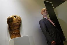 "Dr Uli Sigg of Switzerland poses in front of an art piece by Chinese artist Wang Keping created in 1979, of a wooden sculpture titled ""Chain"", in Hong Kong June 12, 2012. Sigg, the world's leading collector of Chinese contemporary art, on Tuesday donated 1,463 Chinese contemporary artworks, conservatively valued at HK$1.3 billion (US$167 million), to the permanent collection of M+, Hong Kong's future museum for visual culture at West Kowloon Cultural District to be opened in 2017. REUTERS/Bobby Yip"