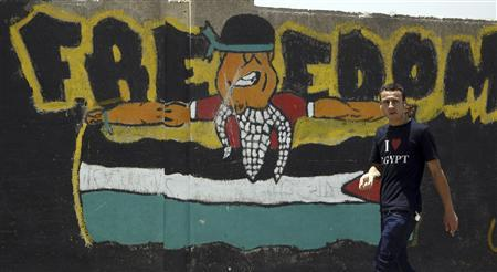 A man walks past a wall paint demanding freedom for Palestine, in Cairo June 12, 2012. REUTERS/Amr Abdallah Dalsh