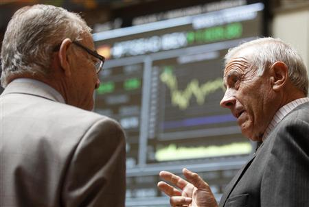 Traders talk next to electronic boards at the stock exchange in Madrid June 12, 2012. REUTERS/Andrea Comas