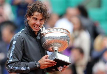 Rafael Nadal of Spain bites the trophy as he poses during the ceremony after defeating Novak Djokovic of Serbia during their men's singles final match at the French Open tennis tournament at the Roland Garros stadium in Paris June 11, 2012. REUTERS/Nir Elias