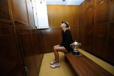 Maria Sharapova of Russia poses with her trophy in the dressing room after winning the women's singles final match against Sara Errani of Italy during the French Open tennis tournament at the Roland Garros stadium in Paris June 9, 2012. REUTERS/Sindy Thomas/FFT/Pool