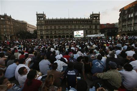 Citizens look to a giant screen during the presidential candidates' televised debate at Zocalo Square in Mexico City June 10, 2012. REUTERS/Edgard Garrido