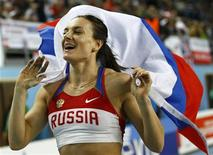 Gold medalist Yelena Isinbayeva of Russia holds her national flag after the women's pole vault final during the world indoor athletics championships at the Atakoy Athletics Arena in Istanbul March 11, 2012. REUTERS/Kai Pfaffenbach
