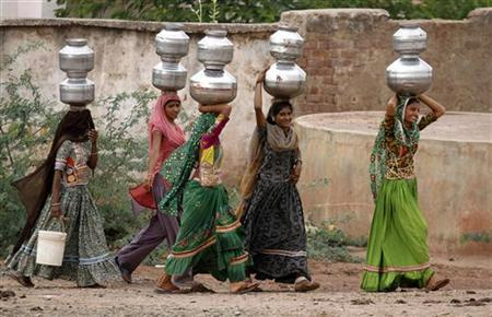 Women carry metal pitchers filled with drinking water at Charnaka village in Patan district of Gujarat April 19, 2012. REUTERS/Amit Dave