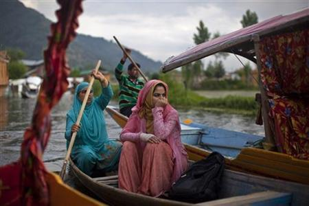 A Kashmiri woman travels in a boat in the waters of Dal Lake in Srinagar June 9, 2012. REUTERS/Ahmad Masood