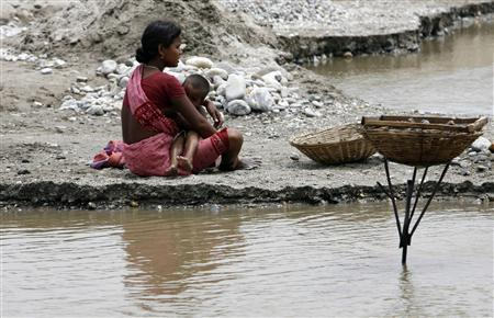 A labourer breastfeeds her child on the banks of the river Balason on Mother's Day on the outskirts of the eastern Indian city of Siliguri in this May 10, 2009 file photo. A Thomson Reuters Foundation survey, polling 370 gender specialists, found Canada to be the best place to be a woman amongst G20 nations, excluding the European Union economic grouping. Saudi Arabia was the second worst, after India. REUTERS/Rupak De Chowdhuri/Files
