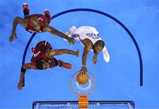 Oklahoma City Thunder forward Kevin Durant (R) dunks the ball against Miami Heat center Joel Anthony (top, L) and forward Chris Bosh during Game 1 of the NBA basketball finals in Oklahoma City, Oklahoma, June 12, 2012. REUTERS/Larry W. Smith/POOL
