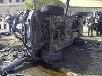 Местные жители стоят около места взрыва бомбы в Багдаде, 13 июня 2012 года. По меньшей мере 44 человека погибли в результате серии взрывов, прогремевших в Багдаде и на юге Ирака в среду, в день крупнейшего религиозного праздника, сообщают источники в полиции и госпитале. REUTERS/Saad Shalash