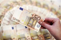 Работница банка в Сараево держит купюру 50 евро, 19 марта 2012 года. Курс евро к доллару стабилизировался в ожидании выборов в Греции, от которых может зависеть будущее страны в еврозоне. REUTERS/Dado Ruvic