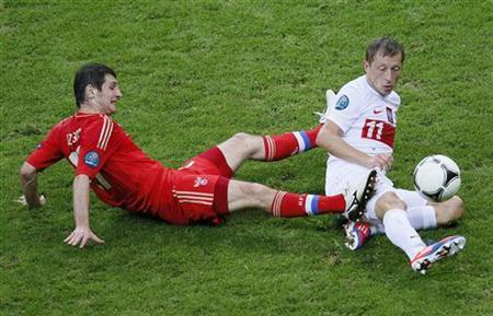 Russia's Alan Dzagoev (L) fights for the ball with Poland's Rafal Murawski during their Group A Euro 2012 soccer match at the National stadium in Warsaw June 12, 2012. REUTERS/Leonhard Foeger