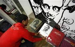 Un inmenso archivo de cartas, documentos y fotografías que arrojan nueva luz sobre el líder indio Mahatma Gandhi y sobre su estancia en Sudáfrica serán subastados en Londres el próximo mes y se espera que alcancen un valor de entre 500.000 y 700.000 libras (entre 620.000 y 869.000 euros). En la imagen, de 31 de octubre de 2010, un hombre coloca camisetas con la imagen de Mahatma Gandhi en una tienda de Nueva Delhi. REUTERS/Adnan Abidi/Files