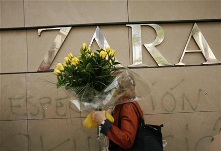 A woman holding a bunch of flowers walks past outside a Zara shop in central Seville March 25, 2009. REUTERS/Marcelo del Pozo
