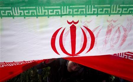 EDITORS' NOTE: Reuters and other foreign media are subject to Iranian restrictions on leaving the office to report, film or take pictures in Tehran. A demonstrator peeks from under an Iranian flag during a ceremony to mark the 33rd anniversary of the Islamic Revolution, in Tehran's Azadi square February 11, 2012. REUTERS/Caren Firouz/Files