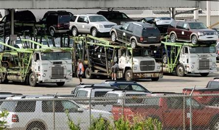 A worker loads Ford Explorers and trucks onto transport trucks at its assembly plant in Louisville, Kentucky, August 24, 2006. REUTERS/John Sommers II