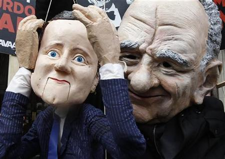 A demonstrator dressed as Rupert Murdoch holds a puppet depicting Britain's Prime Minister David Cameron as he protests outside the High Court in central London April 25, 2012. REUTERS/Suzanne Plunkett