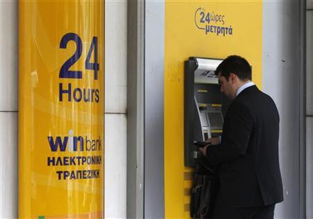 A man makes a transaction at an ATM machine outside a bank branch in central Athens May 24, 2012. REUTERS/John Kolesidis