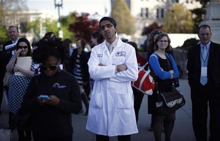Doctor Vivek Murthy stands among other bystanders during the first day of legal arguments over the Affordable Care Act outside the Supreme Court in Washington March 26, 2012. REUTERS/Jason Reed